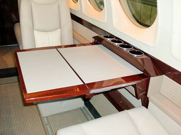 "The King Air 200 armledge table system adds functionality to your cabin and achieve that sought after ""new airplane"" look, and upgrade the cabin to the look and feel of the newest King Airs. The sidewall with integrated outboard armrest rail modernizes"